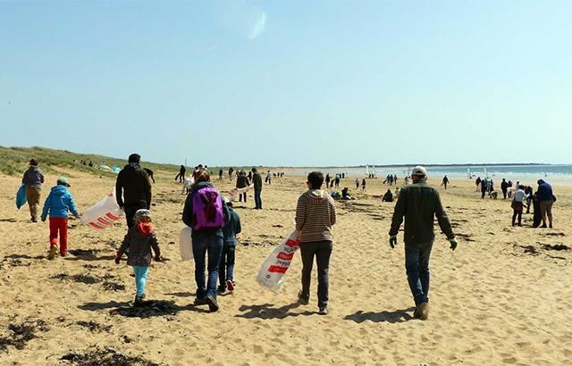 familles marchant sur la plage avec des sacs pour ramasser les déchets